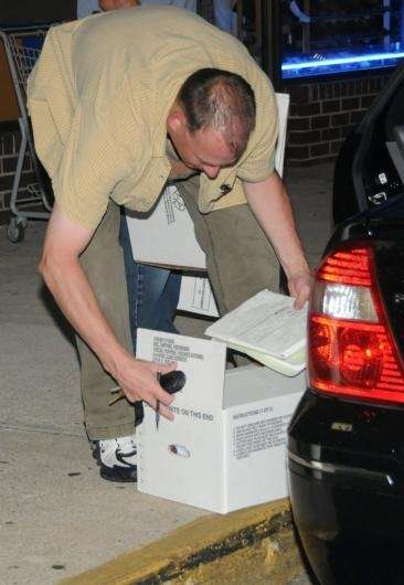 Police collect a box of evidence in front