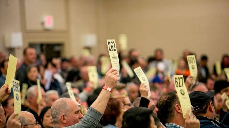 People hold up their auction cards before the