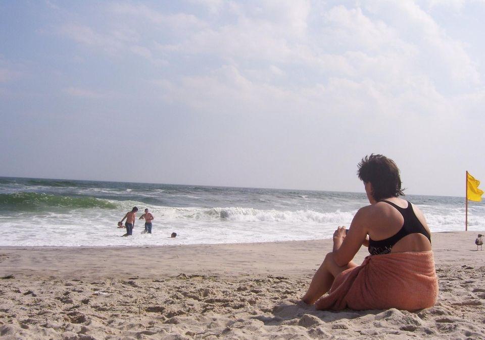 A woman watches the waves at Robert Moses