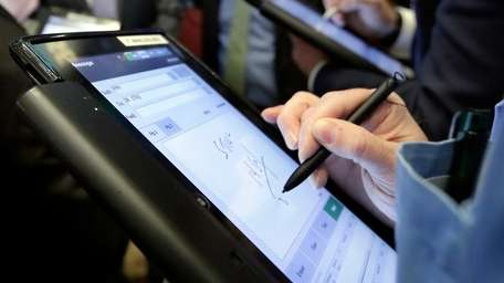 Traders work on their handheld devices on the