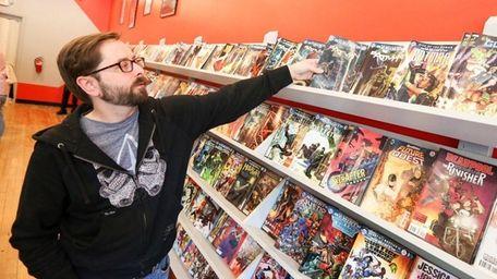 Joshua Darbee, owner of Red Shirt Comics, looks