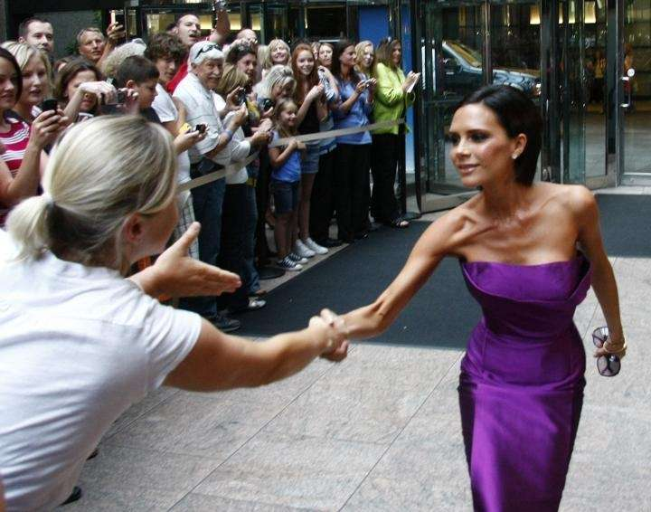 Victoria Beckham greets fans as she arrives at