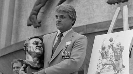Yale Lary poses with his bust and drawing
