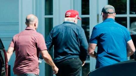 President Donald Trump, in red cap, arrives at