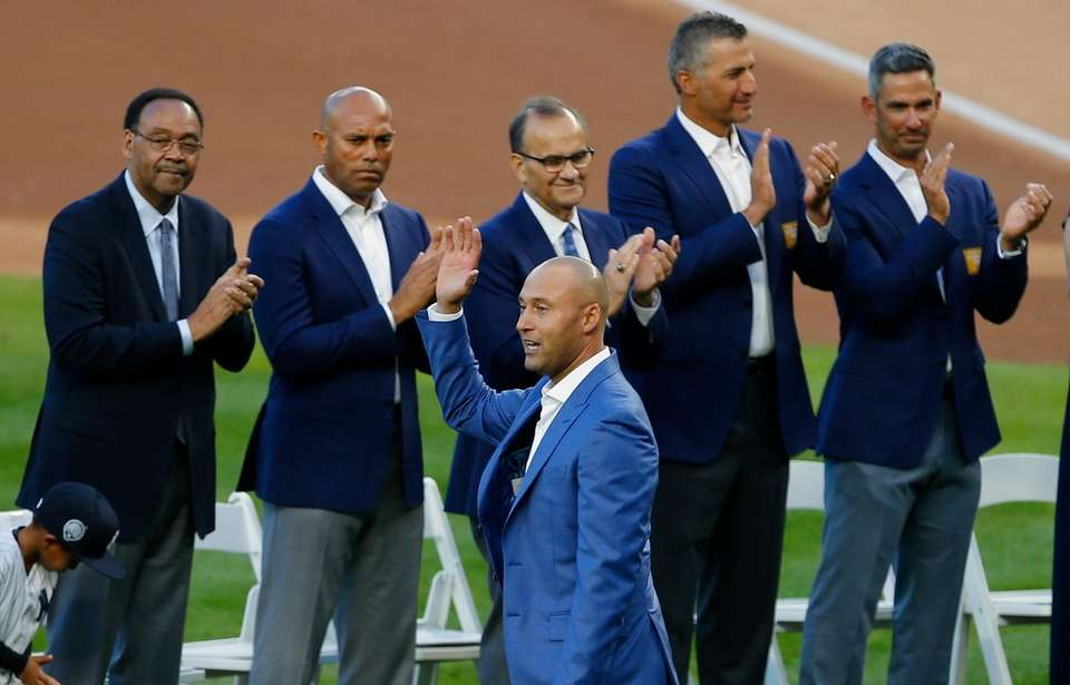 Derek Jeter greets the crowd as his father