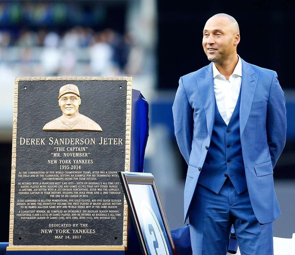 Derek Jeter stands next to his monument park