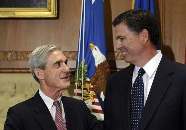 Then-incoming FBI Director James Comey, right, talks with