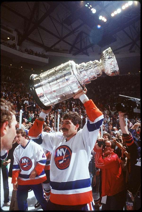Clark Gillies holds up the Stanley Cup at