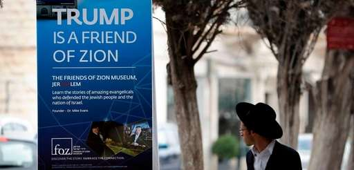 An Ultra-Orthodox Jewish man walks past a poster