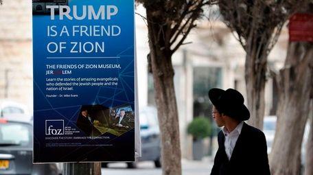An Ultra-Orthodox Jewish man walks past a poster