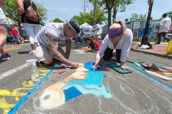 Jim Karanik, a Denver artist, left, works on