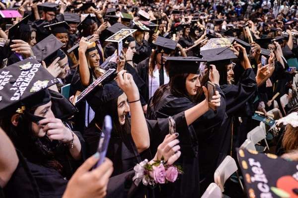 Graduates take selfies while switching their tassels as