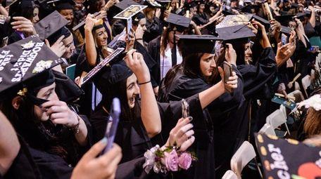 Graduates take selfies while switching their tassels as
