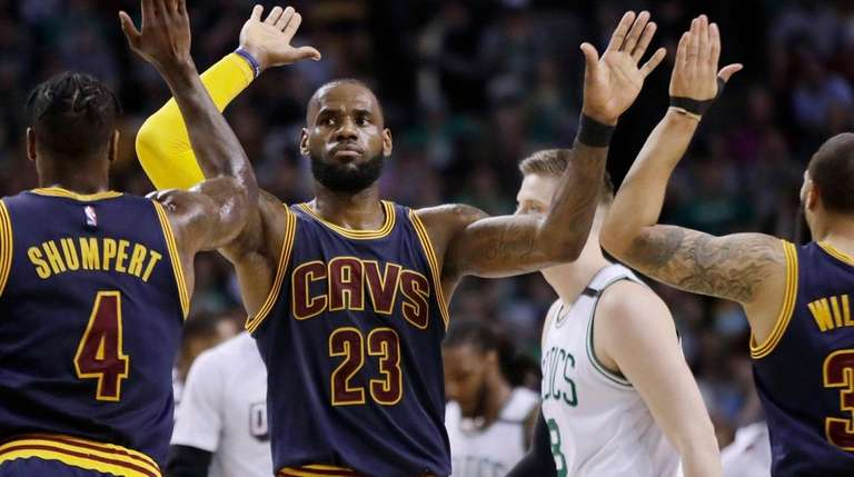 Cleveland Cavaliers forward LeBron James trades high-fives with