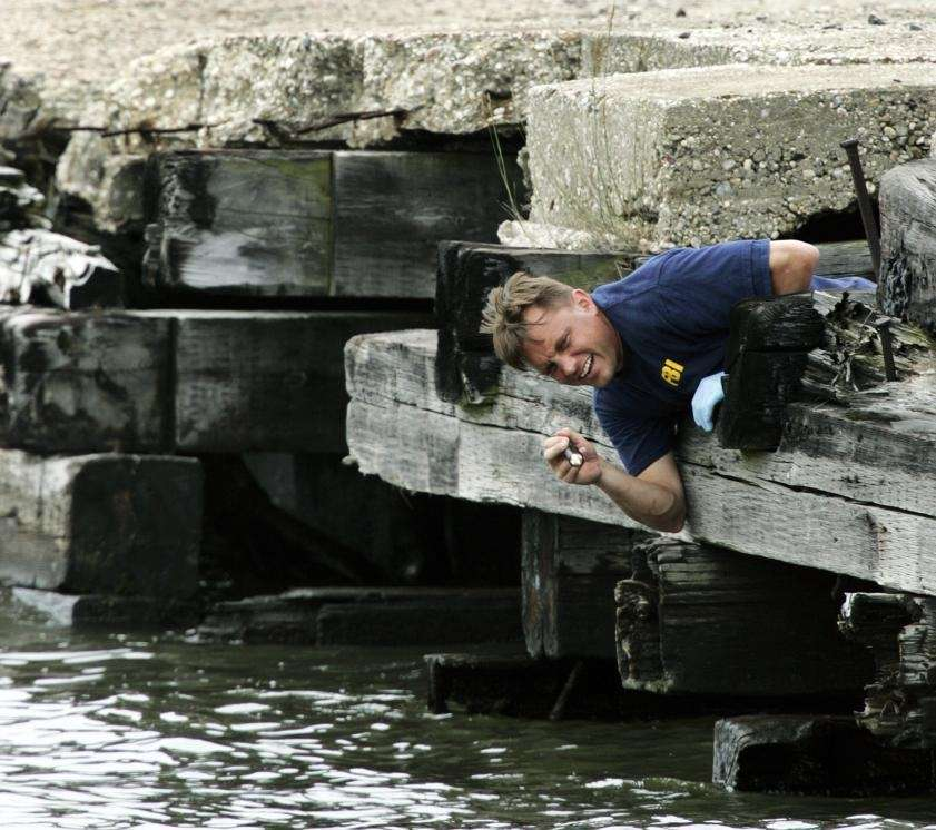 An investigator searches along the Hudson River shore
