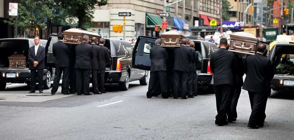 Pallbearers carry coffins to five awaiting hearses at