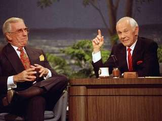 Johnny Carson, behind the desk, with show announcer