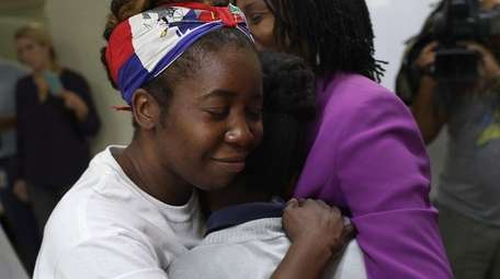 In Miami, Santcha Etienne hugs a 10-year-old girl