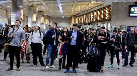 LIRR commuters check the departure board at Penn