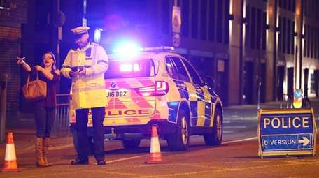 Police stand by a cordoned-off street close to