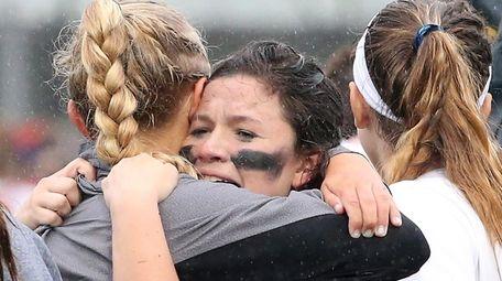 Teammates swarm Long Beach's goalie Sarah Reznick after