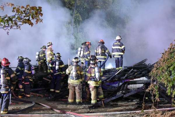 Firefighters work over the remains of a house