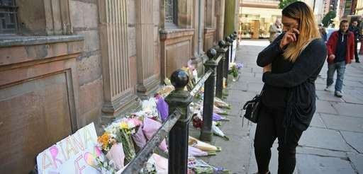 A woman looks at flowers left in St.