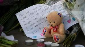 A tribute is laid at a candlelit vigil,