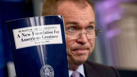 Budget Director Mick Mulvaney holds up a copy