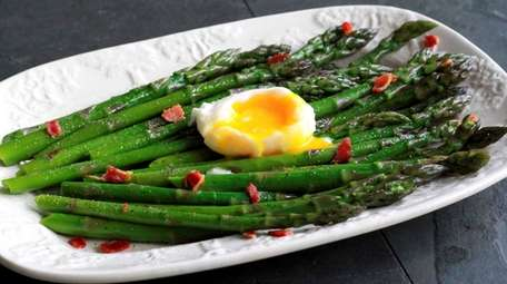 Cooked asparagus topped with crumbled bacon is dressed