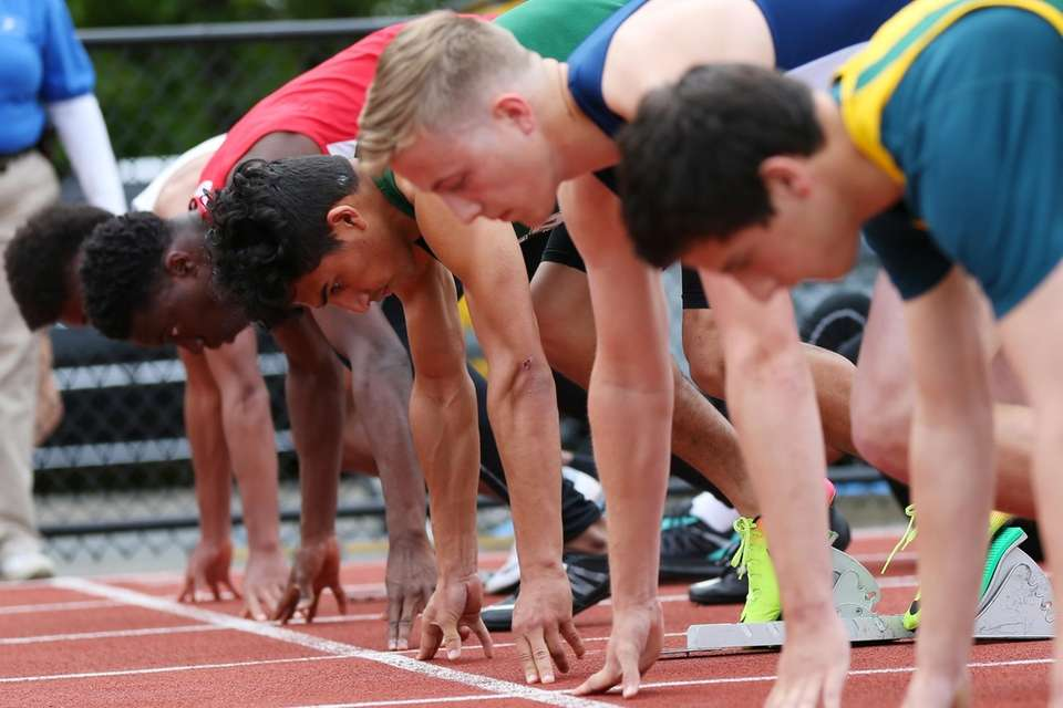 Runners compete in the boys 100 meters during