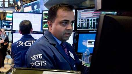Specialist Dilip Patel, right, works with traders on