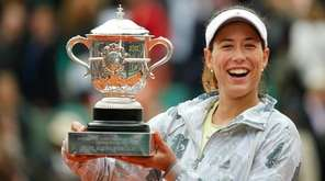 Garbine Muguruza holds the trophy after winning the