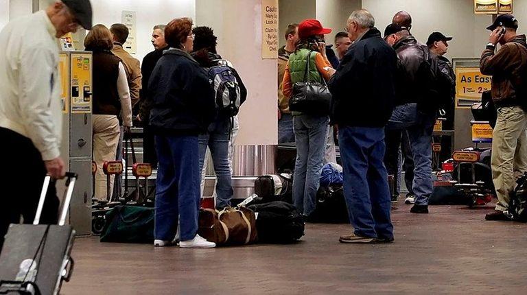 Returning travelers wait at LaGuardia Airport's baggage