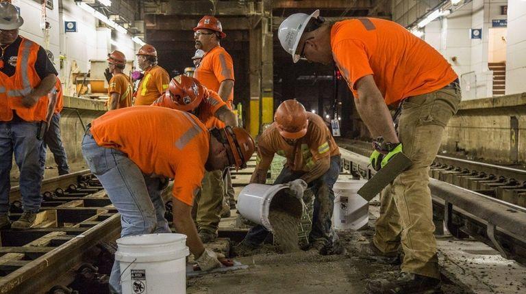 Amtrak crews work on the track at Penn