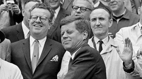 President John F. Kennedy revs up to throw