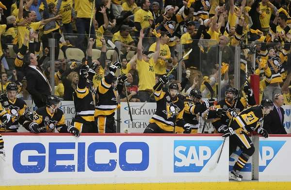 Pittsburgh Penguins players and fans celebrate as the