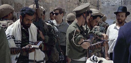 Israeli troops, one in a borrowed prayer shawl,