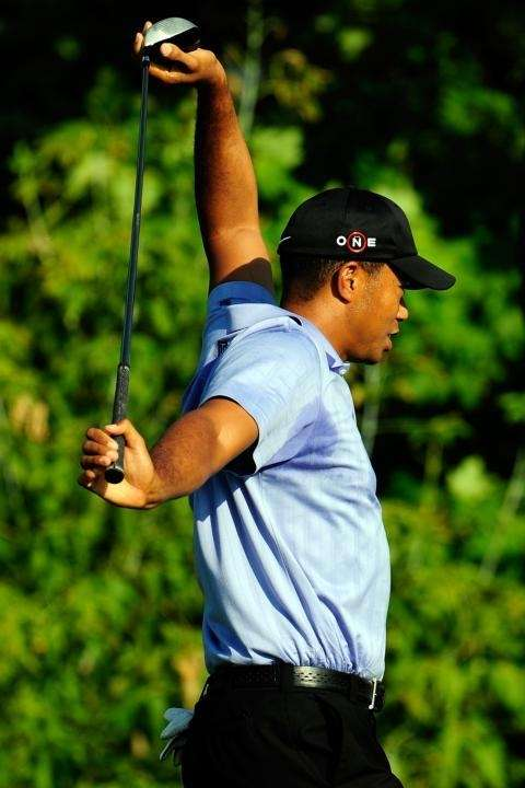 Tiger Woods stretches on the 10th tee during