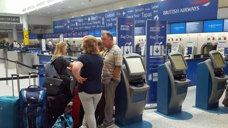 Passengers stand at the British Airways check-in desk