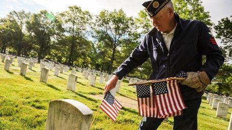 Navy Veteran Tom Taylor, of Farmingdale, places flags