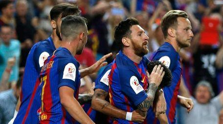 Barcelona's Lionel Messi, second right, celebrates with teammates