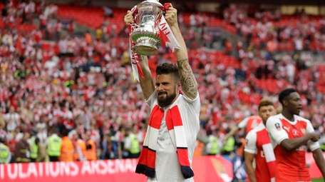Arsenal's Olivier Giroud celebrates with the trophy after