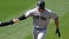 Aaron Judge is greeted by third base