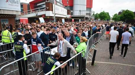 Concert-goers are searched by security as they queue