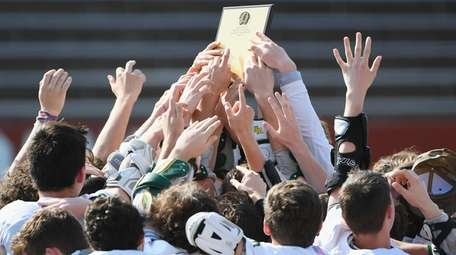 Ward Melville players raise their championship plaque after