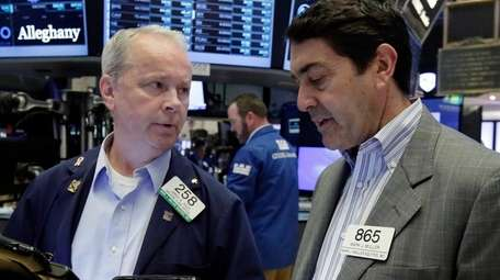 Traders James Riley, left, and Mark Muller work