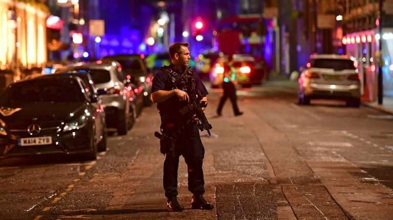 An armed police officer stands on Borough High