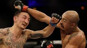 Jose Aldo, of Brazil, right, trades punches with