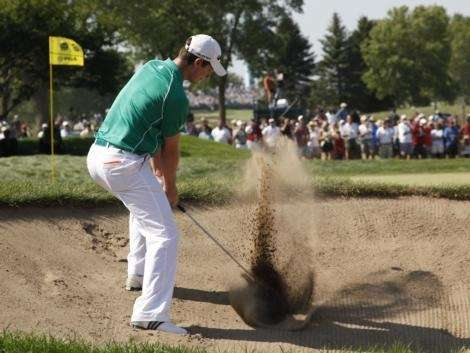 Justin Rose, of England, blasts out of a